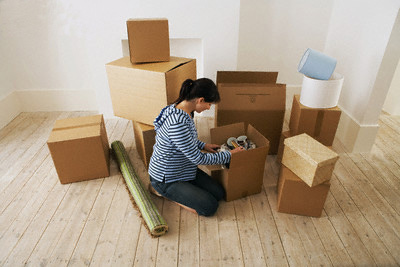 Woman Looking at Contents of Moving Boxes --- Image by © moodboard/Corbis