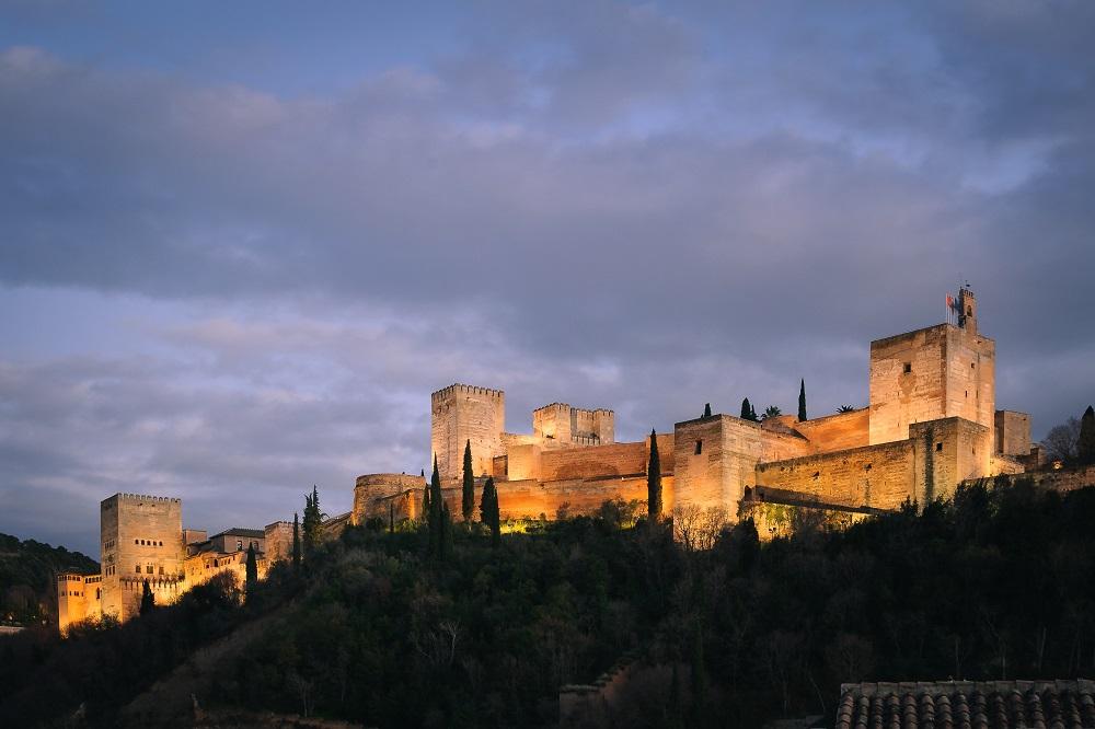 La Alhambra de Granada iluminada de noche con cielo azul